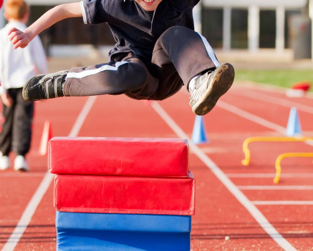 PE lesson boy hurdling in athletics